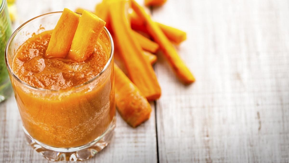 In einem Glas befindet sich ein Karotten-Kartoffel-Brei, daneben liegen einige geschälte Möhren.