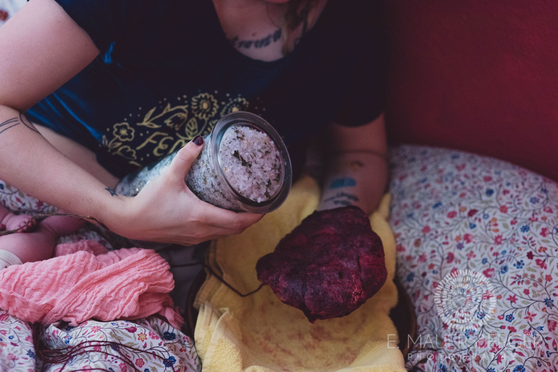 Mutter schüttet mit einem Glas grobkörniges Salz und Kräuter über die Plazenta ihres Babys, die sie in der Hand hält.